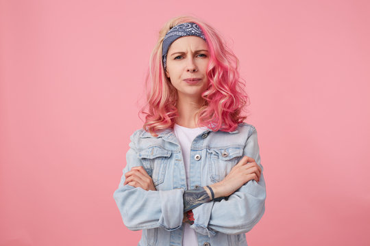 Frowning lady with pink hair and tattooed hand, looking at the camera with disapproval and discontent, standing over pink background with crossed arms, wearing a white t-shirt and denim jacket.