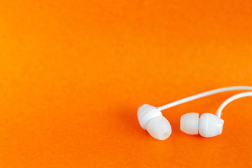 White earbuds on orange colorful background with copy space for text
