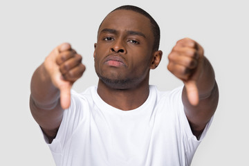 Serious african man showing thumbs down gesture of disapproval