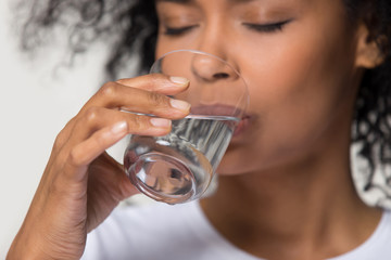 Close up african millennial female holding glass drinking water