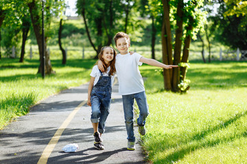 Picture of brother and sister having fun in the summer park on sunset. Cheerful children hugs and laughing. Little girl and boy playing outdoors, best friends, happy family, love and happiness concept
