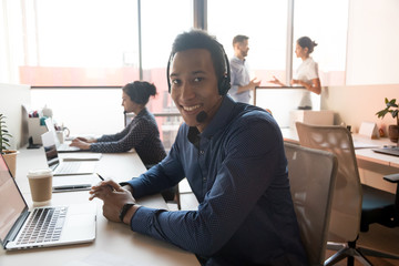Portrait of smiling ethnic male agent in headset at workplace