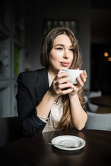 Smiling woman in a good mood with cup of coffee sitting in cafe.