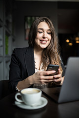 Charming woman with beautiful smile reading good news on mobile phone during rest in coffee shop. Caucasian female watching her photos on cell telephone while relaxing in cafe during free time