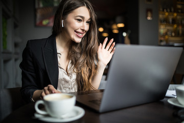 Beautiful young woman working with laptop in a cafe.