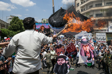 Iranians burn an Israeli flag during a protest marking the annual al-Quds Day (Jerusalem Day) on the last Friday of the holy month of Ramadan in Tehran