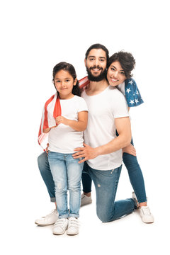 cheerful latin family smiling while holding american flag isolated on white