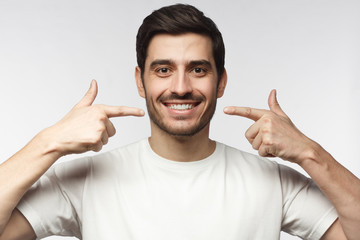Portrait of smiling young man pointing to his perfect natural white teeth after whitening...