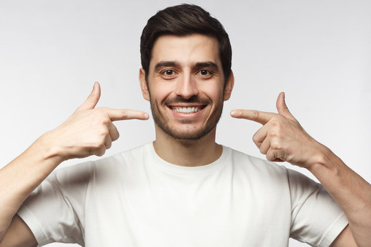 Portrait of smiling young man pointing to his perfect natural white teeth after whitening treatment. Dental clinic ads concept