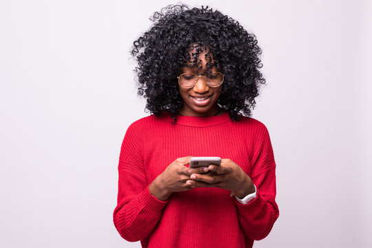 Communicating african woman with afro hairstyle using mobile phone and looking aside on copyspace isolated over white background