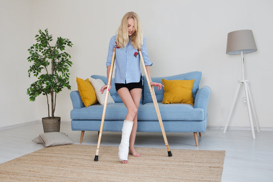 Young woman with crutch and broken leg in cast sitting on sofa at home