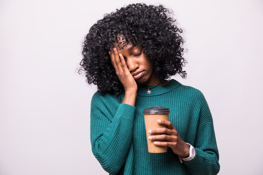 Tired sleepy african woman covers half of face with palm, has sad expression, closes eyes, carries disposable cup of drink containing caffeine, has continue working isolated on white background