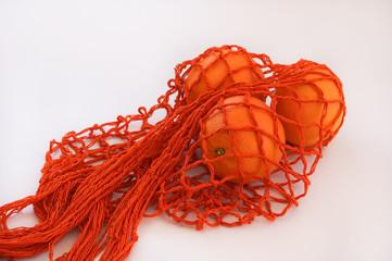 Handmade cotton Orange string bag three oranges white background