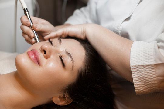Close up side view portrait of a cute caucasian woman doing noninvasive microdermabrasion on her face with a dermapen by a cosmetician.