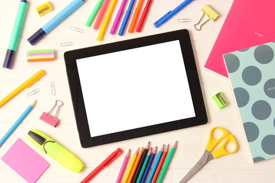 Modern digital tablet and school stationery on a colored background top view. Kontpt back to school. Place for text.