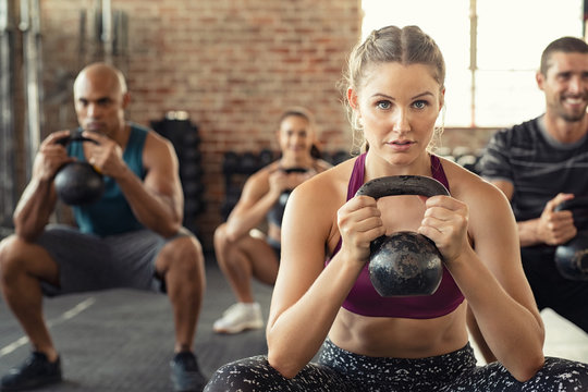 Fitness woman squatting with kettle bell