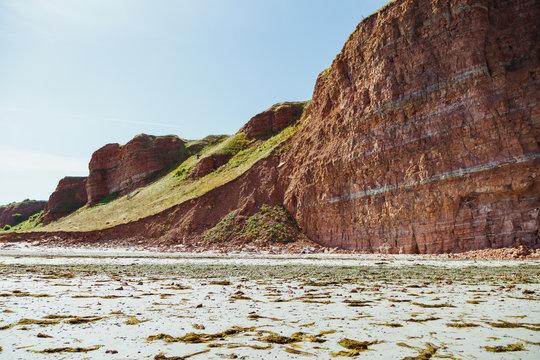 Rote Felsküste an weißem Sandstrand
