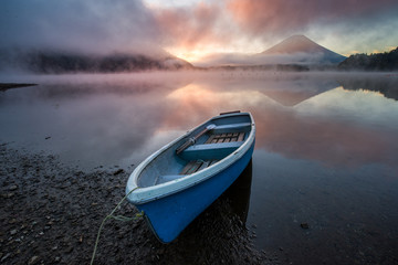 Obraz Beautiful mystical sunrise at Lake Shōji with Mount Fuji as a backdrop and a row boat in the foreground - fototapety do salonu
