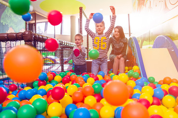 young mom playing with kids in pool with colorful balls