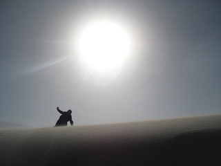 Silhouette of man in desert on sunset background of the sky