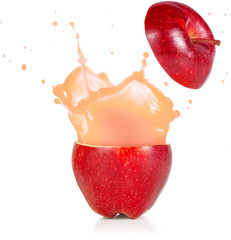 Wall Mural - juice exploding out of a red apple isolated on white.