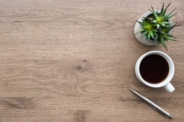 Wall Mural - Wood office desk table with cup of coffee, pen and cactus pot. Top view with copy space, flat, lay.