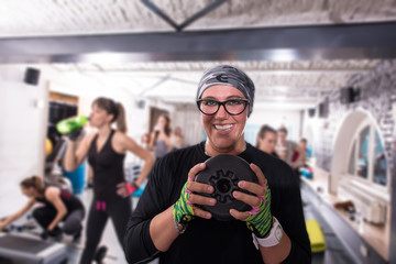sporty woman holding a metal round weights plate