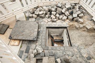 Strassenbauarbeiten um einen kleinen Kabelschacht aus Beton