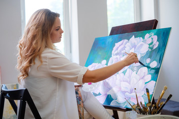 Creative painter paints a colorful picture in her studio