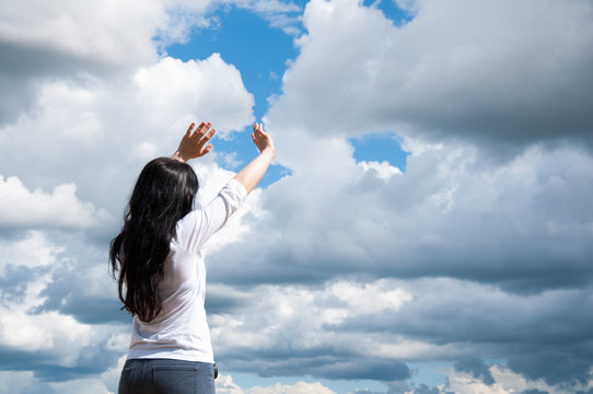 a woman with her arms raised praises God or prays. Against the blue sky and white clouds