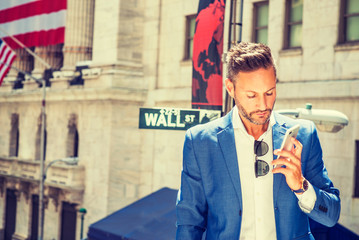 Young European Businessman with beard traveling, working in New York City, wearing blue blazer, sunglasses hanging on white shirt, standing on Wall Street, looking at cell phone, taking phone call..
