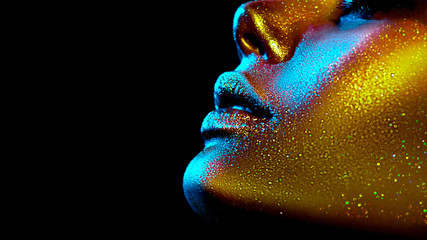 Wall Mural - Fashion model woman skin face in bright sparkles, colorful neon lights, beautiful sexy girl lips, mouth. Trendy glowing gold skin make-up. Art design make up. Glitter metallic shine makeup