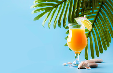 Orange summer alcoholic cocktail with mango juice, rum, liqueur, lime and ice, blue background, copy space