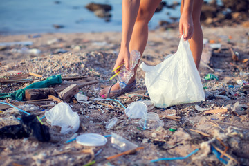 Woman collect garbage on the beach. Environmental pollution concept