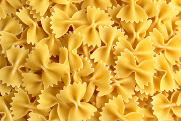 The texture of pasta in the form of a bow on a pink background