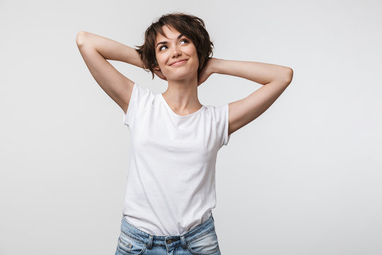 Image of optimistic woman in basic t-shirt touching her hair and looking aside