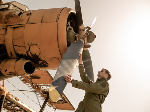 A handsome young pilot standing next to the propeller