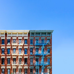 Fototapete - Old New York City apartment building exterior with fire escapes and windows and empty blue sky above in the Alphabet City Neighborhood of Manhattan