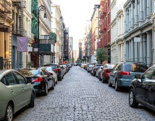 Cobblestone covered Greene Street is crowded with buildings and cars in the SoHo neighborhood of Manhattan in New York City