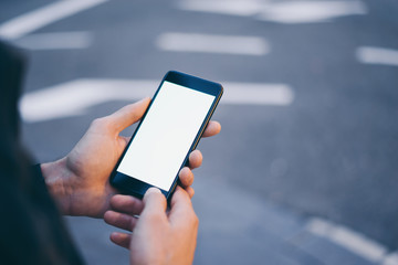 Closeup image of male hand holding smartphone with blank screen. Mockup ready for text message or content. Man's hands with cellphone. Empty display. Night street, bokeh light Fotomurales