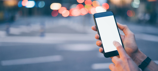 Closeup image of male hand holding smartphone with blank screen. Mockup ready for text message or content. Man's hands with cellphone. Empty display. Night street, bokeh light