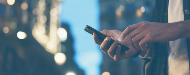 Closeup image of male hands with smartphone at night on city street, searching internet or social networks, hipster man typing an sms message on chat