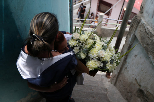 Jennifer Guerrero, mother of Erick Altuve, a 11-year-old boy who died from respiratory problems while in care for stomach cancer at the public Jose Manuel de los Rios hospital, is comforted by a friend during Erick's wake at Petare neighborhood in Caracas