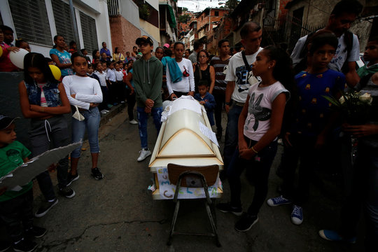 Relatives stand next to the coffin containing the body of Erick Altuve, a 11-year-old boy who died from respiratory problems while in care for stomach cancer at the public Jose Manuel de los Rios hospital, outside his school in Caracas