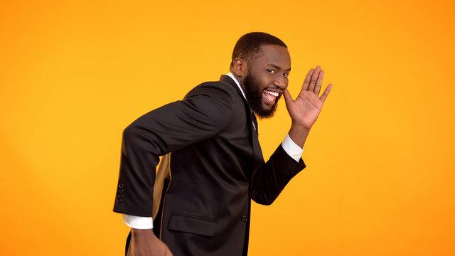 Joyful handsome afro-american man pretend running, black friday sale, discounts