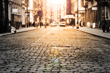 Fotomurales - New York City - Cobblestone street view in Soho with sunlight background in black and white