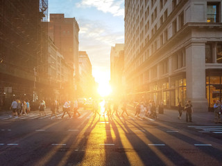 Fotomurales - View of a busy intersection in Manhattan with sunlight shining on crowds of people in New York City