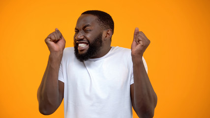 Satisfied Afro-American man extremely happy, jackpot winning, luck and fortune