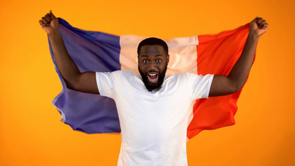 Excited black man holding French flag, supporting national sports team, cheering