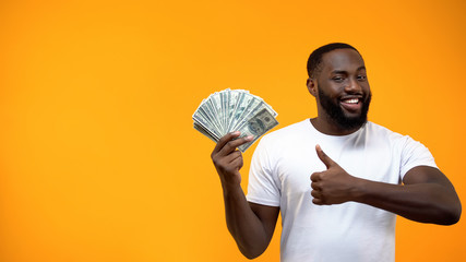 Afro-American man holding bunch of dollars and showing thumbs up, start-up